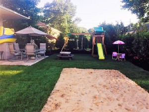 Landscape design with sod and sand added for family fun.